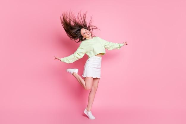 Pełnej długości zdjęcie profilowe atrakcyjnego młodzieńca pani podnosić ramiona nogi taniec studentów party fryzura lot nosić casual crop sweter nagi brzuch spódnica buty na białym tle różowy kolor tła