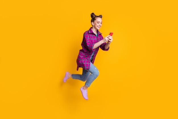 Pełnej długości zdjęcie profilowe ładnej nastolatki pani skacze wysoko podekscytowany dobry nastrój przeglądanie telefonu i poruszanie się na ulicy dorywczo koszula w kratę trampki dżinsy na białym tle żółty żywy kolor tła