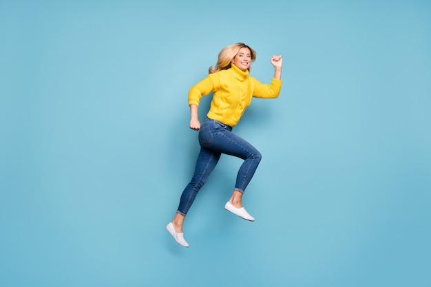 Pełnej długości zdjęcie profilowe ładnej pani skaczącej w pośpiechu w centrum handlowym niskie ceny na zakupy nosić dzianiny żółty sweter dżinsy na białym tle niebieski kolor ściany