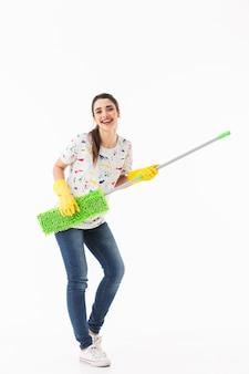 Pełnej długości zdjęcie radosnej gospodyni domowej w wieku 20 lat w żółtych gumowych rękawiczkach do ochrony rąk, bawiącej się podczas mycia podłogi mopem na białym tle nad białą ścianą