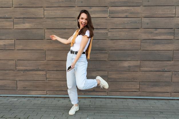 Pełnej długości zdjęcie rozmiaru ciała młodej szczęśliwej kobiety noszącej zwykłe ubrania i słuchającej
