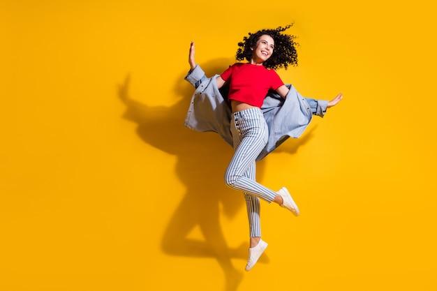 Pełnej długości zdjęcie słodkiej damy wygląda na pustą przestrzeń skok nosić paski dżinsy przycięte czerwona koszulka kurtka trampki na białym tle żółty kolor tła
