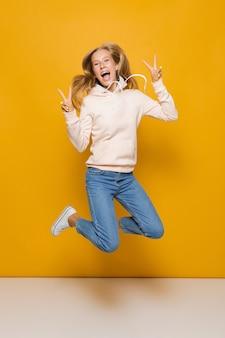 Pełnej długości zdjęcie słodkiej uczennicy z aparatami ortodontycznymi, skaczące i pokazujące znak pokoju, odizolowane na żółtym tle