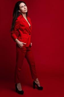 Pełnej długości zdjęcie stockowe pewnej siebie ładnej kobiety z długimi ciemnymi włosami, ubranej w jaskrawoczerwoną kurtkę