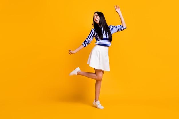 Pełnej długości zdjęcie szczerej podekscytowanej energicznej dziewczyny ciesz się tańcem letniej dyskoteki nosić stylowe ubrania trampki odizolowane na tle koloru połysku