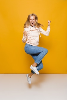 Pełnej długości zdjęcie uroczej dziewczyny z aparatami ortodontycznymi, skaczące i zaciskające pięści, odizolowane na żółtym tle
