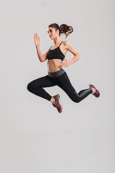 Pełnej długości zdjęcie w profilu szczęśliwej zdrowej kobiety w odzieży sportowej z abs skoki i latanie, odizolowane na szarej ścianie