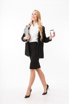 Pełnej długości zdjęcie wesoła bizneswoman w garniturze biurowym spacerująca z laptopem i kawą na wynos, odizolowana
