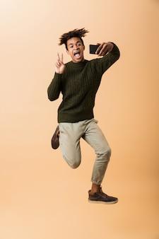 Pełnej długości zdjęcie wesoły afroamerykanin w swetrze, biorąc selfie na smartfonie, na białym tle nad beżową ścianą