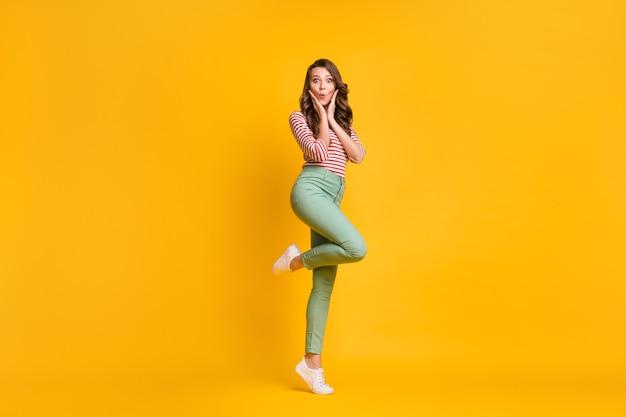 Pełnej długości zdjęcie wielkości ciała dziewczyny stojącej na palcach zdumionej dotykającej kości policzkowych na jasnożółtym tle