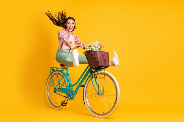 Pełnej długości zdjęcie wielkości ciała funky dziewczyny jadącej na rowerze trzymającej nogi krzyczące na jasnożółtym tle