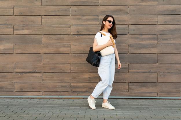 Pełnometrażowa młoda, urocza piękna brunetka kobieta idzie na ulicy w pobliżu brązowej ściany