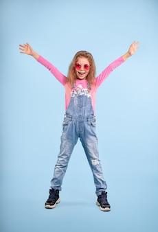 Pełnometrażowa radosna preteen dziewczyna ubrana w dżinsowy kombinezon i różowe stylowe okulary przeciwsłoneczne, stojąca z rozpostartymi ramionami