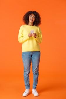 Pełnometrażowe pionowe ujęcie marzycielskiej uroczej afroamerykańskiej kobiety zastanawiającej się, co napisać, trzymając smartfon myślący, patrząc w górę i uśmiechając się, wyobrażając sobie rzeczy, stojąc radośnie na pomarańczowej ścianie.