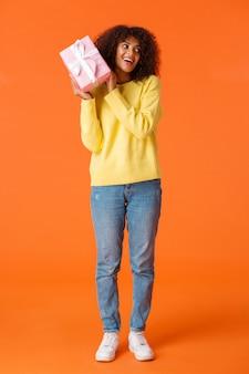 Pełnometrażowe ujęcie ciekawa urocza afroamerykańska dziewczyna otrzymuje świąteczny prezent i interesuje się tym, co jest w środku, potrząsając pudełkiem prezentowym zgadnij co tam, uśmiechając się, świętując zimowe wakacje