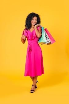Pełnometrażowe zdjęcie afroamerykanki w różowej sukience i butach na wysokim obcasie, która pozuje stojąc na prawej nodze w półprofilu z torbami na zakupy na lewym ramieniu