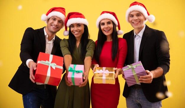 Pełnometrażowe zdjęcie czterech elegancko ubranych ludzi, dwóch kobiet i dwóch mężczyzn, w czerwonych noworocznych czapkach i pozujących z ładnie zapakowanymi prezentami o różnej wielkości i kolorze.