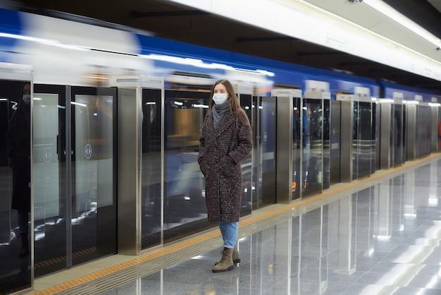 Pełnometrażowe zdjęcie kobiety w masce medycznej czekającej na nadjeżdżający metrem nowoczesny pociąg