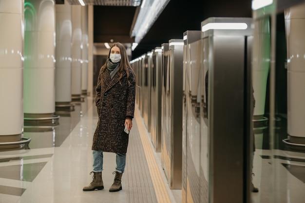 Pełnometrażowe zdjęcie kobiety w medycznej masce na twarz, aby uniknąć rozprzestrzeniania się covid, czeka na pociąg i trzyma telefon na peronie metra. dziewczyna w masce chirurgicznej trzyma dystans społeczny