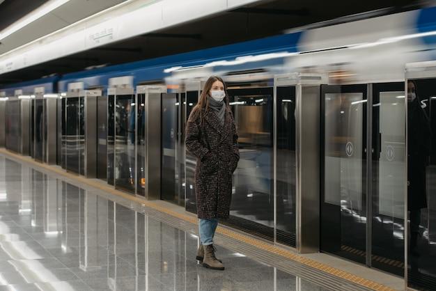 Pełnometrażowe zdjęcie kobiety w medycznej masce na twarz, aby uniknąć rozprzestrzeniania się koronawirusa, która czeka na nadjeżdżający nowoczesny pociąg w metrze. dziewczyna w masce chirurgicznej zachowuje dystans społeczny.
