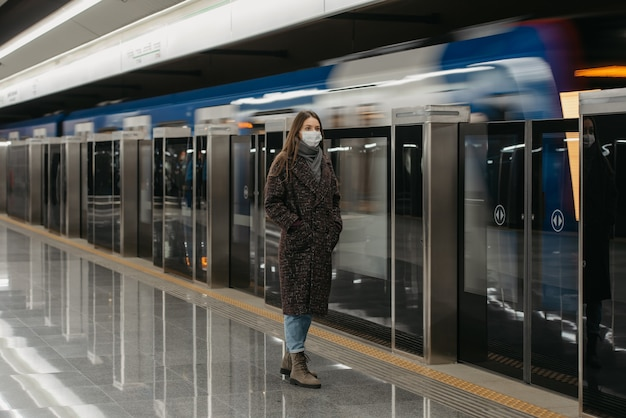 Pełnometrażowe zdjęcie kobiety w medycznej masce na twarz, aby uniknąć rozprzestrzeniania się koronawirusa, która czeka na przyjeżdżający pociąg na peronie metra. dziewczyna w masce chirurgicznej trzyma dystans społeczny