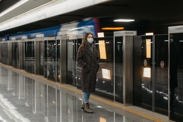 Pełnometrażowe zdjęcie kobiety w medycznej masce na twarz, aby uniknąć rozprzestrzeniania się koronawirusa, która czeka na przyjeżdżający pociąg na peronie metra. dziewczyna w masce zachowuje dystans społeczny.
