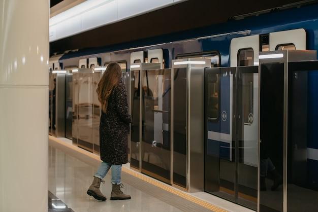 Pełnometrażowe zdjęcie kobiety w medycznej masce na twarz, aby uniknąć rozprzestrzeniania się koronawirusa, która jedzie do nowoczesnego metra. dziewczyna w masce chirurgicznej utrzymuje dystans społeczny na stacji metra.