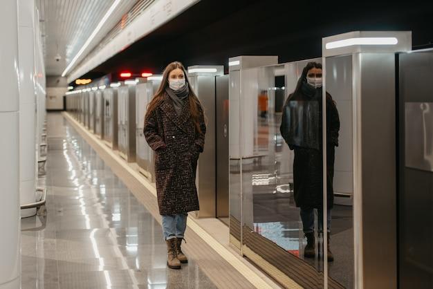 Pełnometrażowe zdjęcie kobiety w medycznej masce na twarz, aby uniknąć rozprzestrzeniania się koronawirusa, która stoi na peronie metra. dziewczyna w masce trzyma dystans społeczny.