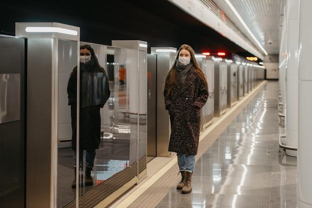 Pełnometrażowe zdjęcie kobiety w medycznej masce na twarz, aby uniknąć rozprzestrzeniania się koronawirusa, która stoi na peronie metra. dziewczyna w masce zachowuje dystans społeczny.