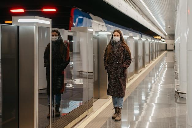 Pełnometrażowe zdjęcie kobiety w medycznej masce na twarz, aby uniknąć rozprzestrzeniania się koronawirusa, która stoi w pobliżu odjeżdżającego pociągu na peronie metra. dziewczyna w masce zachowuje dystans społeczny.