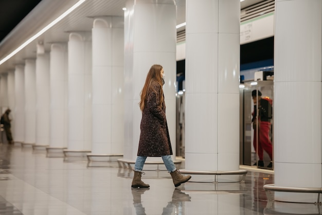 Pełnometrażowe zdjęcie kobiety w medycznej masce na twarz, aby uniknąć rozprzestrzeniania się koronawirusa, który wchodzi na peron metra. dziewczyna w masce chirurgicznej utrzymuje dystans społeczny na stacji metra.