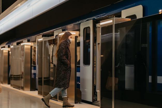 Pełnometrażowe zdjęcie kobiety w medycznej masce na twarz, aby uniknąć rozprzestrzeniania się koronawirusa, który wjeżdża do nowoczesnego metra. dziewczyna w masce chirurgicznej utrzymuje dystans społeczny na stacji metra.