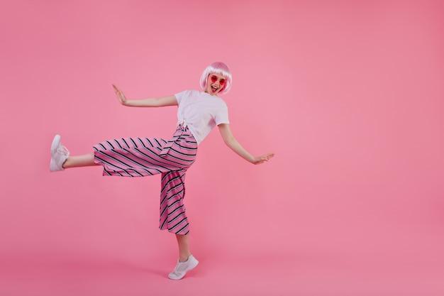 Pełnometrażowe zdjęcie niesamowitej stylowej dziewczyny w tańczących różowych spodniach. portret zadowolona młoda kobieta w eleganckich perukach wyrażających pozytywne emocje