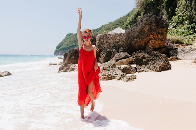 Pełnometrażowe zdjęcie ślicznej kaukaskiej dziewczyny zabawny taniec na plaży. wyrafinowana kobieta ubrana w czerwoną sukienkę chłodzi rano na dzikiej plaży.