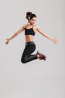 Pełnometrażowe zdjęcie szczupłej, ładnej kobiety w sportowej bieliźnie z silnymi mięśniami brzucha, skaczącą i bawiącą się w siłowni, na białym tle na szarej ścianie