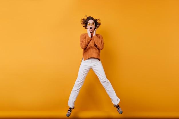 Pełnometrażowe zdjęcie tańczącej zdumionej młodej kobiety w białych spodniach