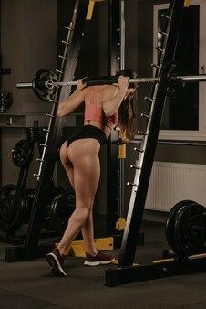 Pełnometrażowe zdjęcie wysportowanej kobiety, która podnosi sztangę, by wykonywać przysiady na stojaku do przysiadów na siłowni. umięśniona brunetka ubrana w koralowy top i krótkie spodenki z wysokim stanem ćwiczy nogi