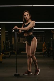 Pełnometrażowe zdjęcie wysportowanej kobiety pozującej z rękami na krótkiej pionowej sztangi na siłowni. umięśniona brunetka ma na sobie czarny top i krótkie spodenki z wysokim stanem.