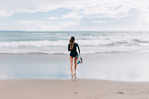Pełnometrażowe zdjęcie z tyłu atrakcyjnej młodej kobiety z długimi włosami ubranej w strój kąpielowy biega w oceanie z deską surfingową, w tle ocean, sport, aktywny tryb życia