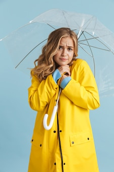 Pełnometrażowy obraz eleganckiej kobiety w wieku 20 lat w żółtym płaszczu przeciwdeszczowym stojącej pod przezroczystym parasolem