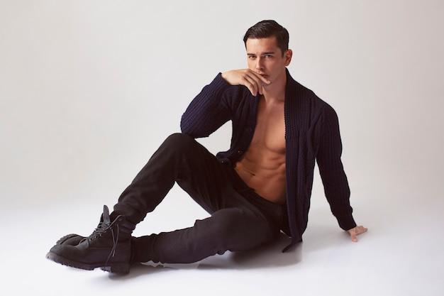 Pełnometrażowy obraz mężczyzny z nagim torsem w czarnych ubraniach.
