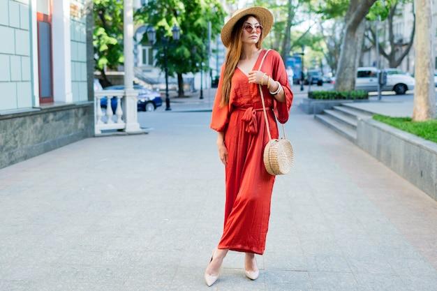 Pełnometrażowy obraz modnej kobiety spędzającej wakacje w europejskim mieście. ubrana w niesamowitą modną koralową sukienkę boho, szpilki, słomkową torbę.