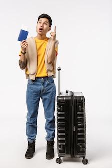 Pełnometrażowy pionowy model azjatycki mężczyzna 20s w żółtej koszulce, dżinsach, uniesionym palcu wskazującym gest eureka, mam świetny pomysł, wymyślił podróż, trzymając paszport, stojące lotnisko z bagażem
