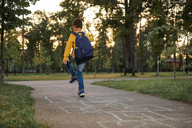 Pełnometrażowy portret aktywnego ucznia korzystającego z rekreacji, grającego w klasy na ziemi po pierwszym dniu w szkole. gry uliczne dla dzieci w klasyce.