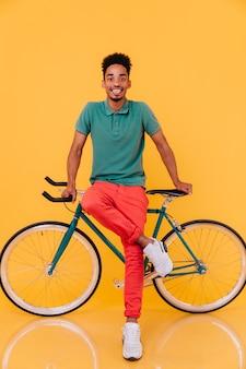 Pełnometrażowy portret beztroskiego rowerzysty w czerwonych spodniach. kryty zdjęcie aktywnego mężczyzny afrykańskiego, ciesząc się z rowerem.