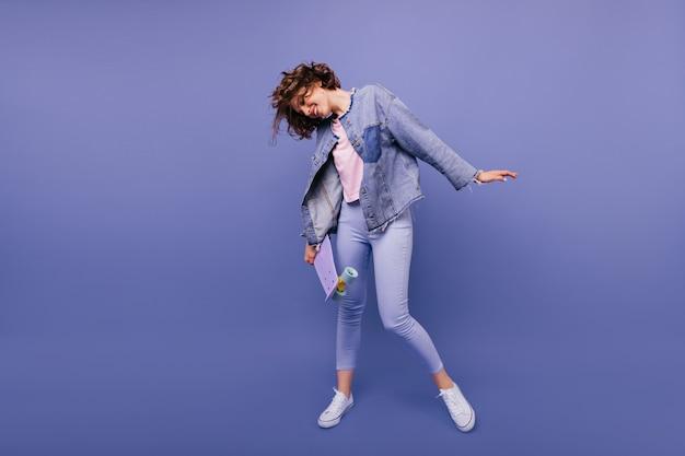 Pełnometrażowy portret beztroskiej modelki z deskorolką pozuje z uśmiechem. fotografia wewnętrzna atrakcyjnej stylowej kobiety w dżinsowej kurtce
