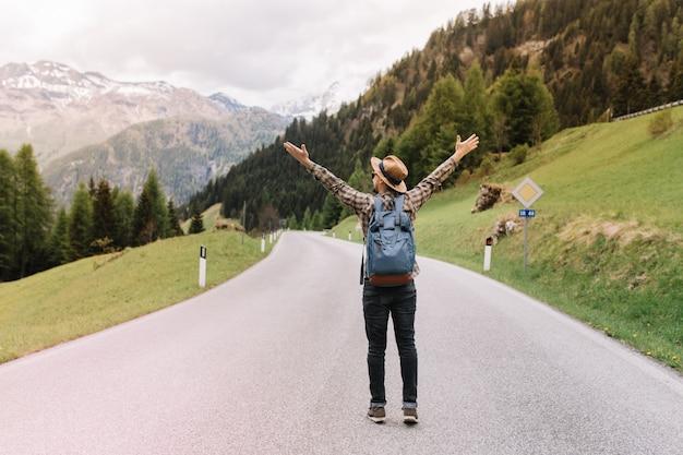 Pełnometrażowy portret błogiego mężczyzny z plecakiem, emocjonalnie pozującego z podniesionymi rękami i autostopem na autostradzie