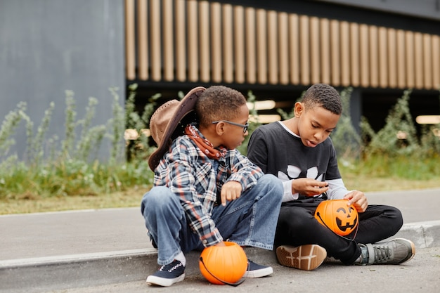 Pełnometrażowy portret dwóch chłopców z afryki, trzymających halloweenowe wiadra, siedzących na krawężniku...