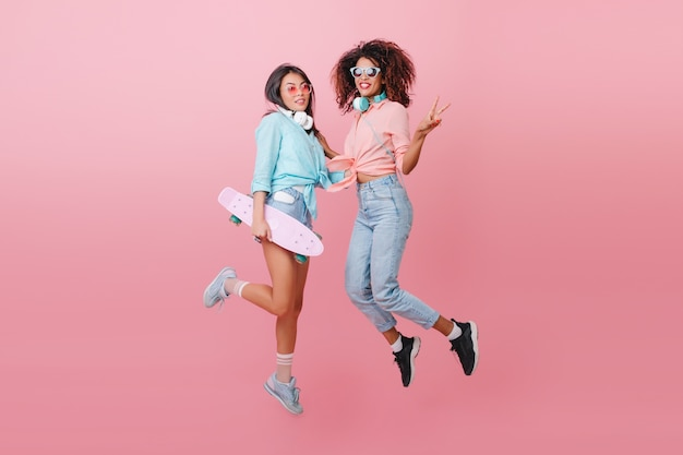 Pełnometrażowy portret dwóch wysportowanych pań skaczących i uśmiechniętych. glamorous skater dziewczyna w niebieskiej koszuli, zabawy z afrykańską przyjaciółką w czarnych butach.
