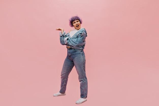 Pełnometrażowy portret emocjonalnej kobiety w białych trampkach i obcisłych dżinsach. zdziwiona kobieta z fioletowymi włosami, pozowanie na różowo.